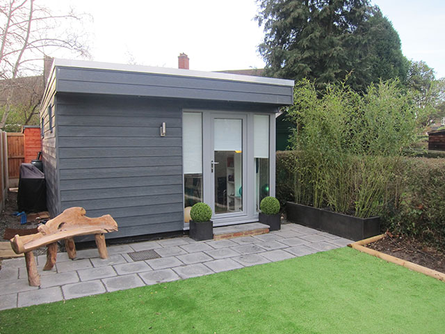 The garden room is clad with Cedral Weathboard, which has a ...